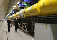 Workers walk past the first section of the European XFEL linear accelerator, which has been nearly completely assembled in the tunnel. Image courtesy of DESY