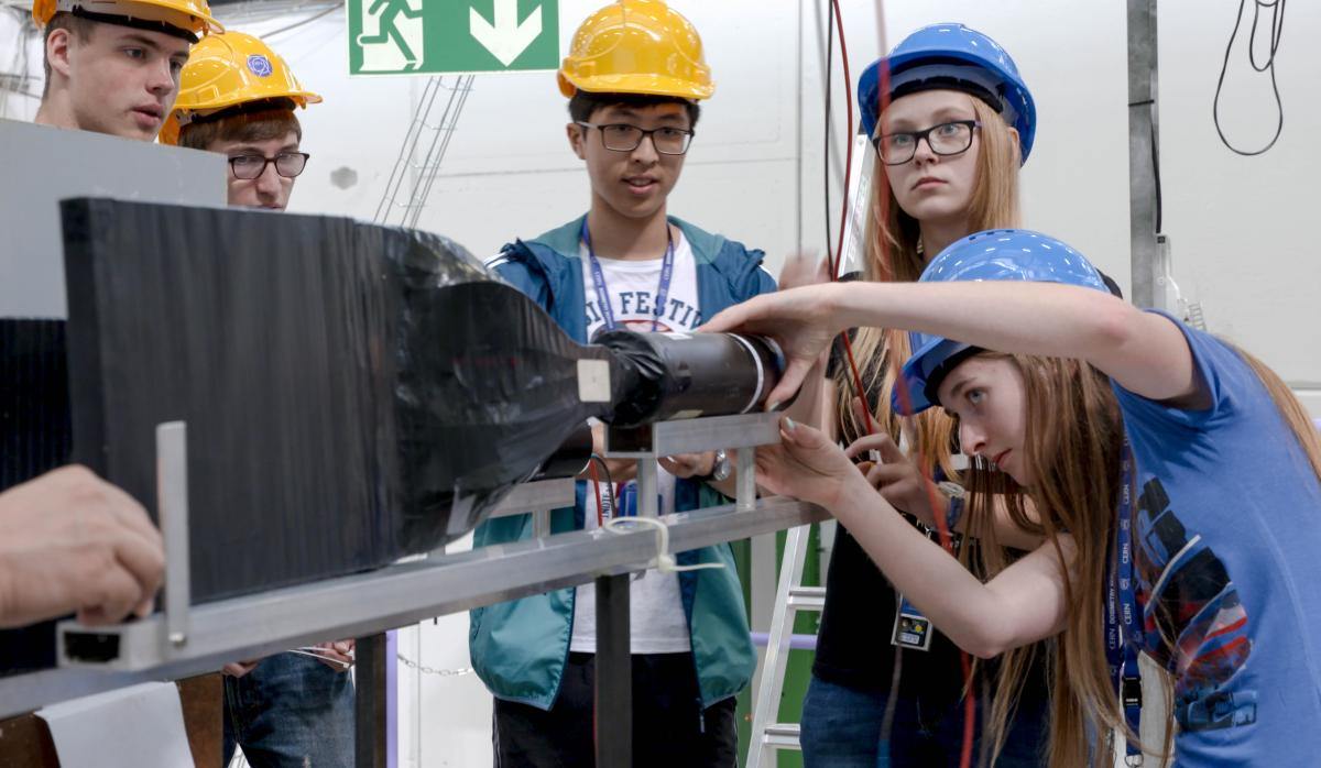 Students from the 2016 winning teams helping each other to set up their experiments in the beamline