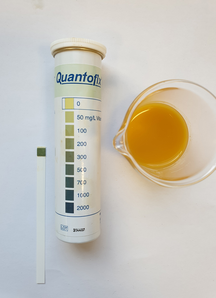 Vitamin C test strip and scale after immersion in orange juice