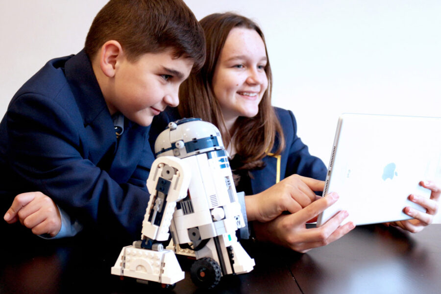 Children with a small R2-D2 model looking at a tablet.