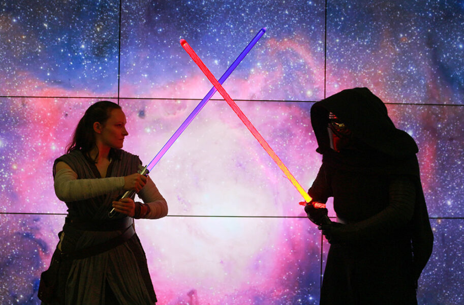 Demonstrators dressed as a Jedi and a Sith fighting with lightsabers.