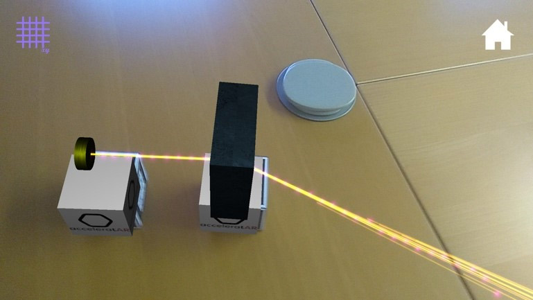 A screenshot of acceleratAR app with the particle source and dipole magnet cubes, showing the virtual light beam being redirected.