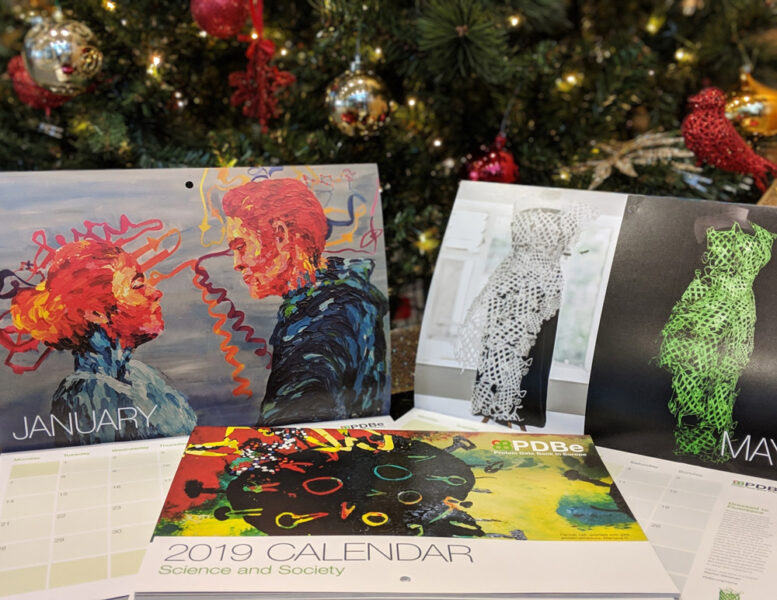 PDB Art calendars from previous years on display in front of a Christmas tree.